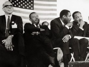 Dr.-Benjamin-Spock-Rev.-Ralph-Abernathy-Dick-Gregory-talks-with-Dr.-Martin-Luther-King-on-stage-by-Bettmann-Archive-300x226, Dick Gregory, Culture Currents