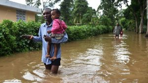 After-Hurricane-Irma-man-carries-child-flooded-street-Fort-Liberte-Haiti-090817-by-CNN-300x169, The Caribbean is being killed: Time to fight back, World News & Views