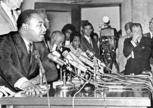 Martin-Luther-King-says-LAPD-Chief-Wm.-H.-Parker-shd-resign-after-65-Watts-Rebellion-as-Mayor-Sam-Yorty-covers-face-press-conf-LA-City-Hall-081965-by-Larry-Sharkey-LA-Times-300x213, Acting Mayor London Breed honors Dr. King and reports progress in supporting homeless and immigrant San Franciscans, Local News & Views
