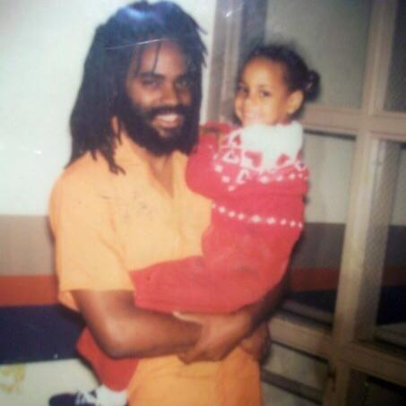 Mumia-holds-lil-daughter-Samiya-bka-Goldii-Graterford-awaiting-trial-1981, New appeal to free Mumia! Endorse today!, Behind Enemy Lines