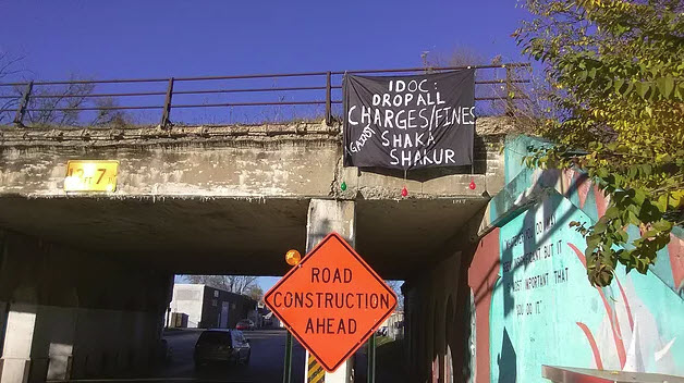 IDOC-Drop-all-charges-fines-against-Shaka-Shakur'-banner-drop-over-highway, Shaka Shakur: Help resuscitate justice in Sullivan County, Behind Enemy Lines