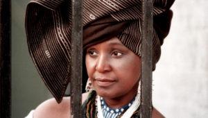 Winnie-Mandela-behind-barred-gate-Soweto-home-defying-banishment-to-Orange-Free-State-1986-by-David-Turnley-Corbis-300x170, Winnie Madikizela Mandela (1936-2018), World News & Views