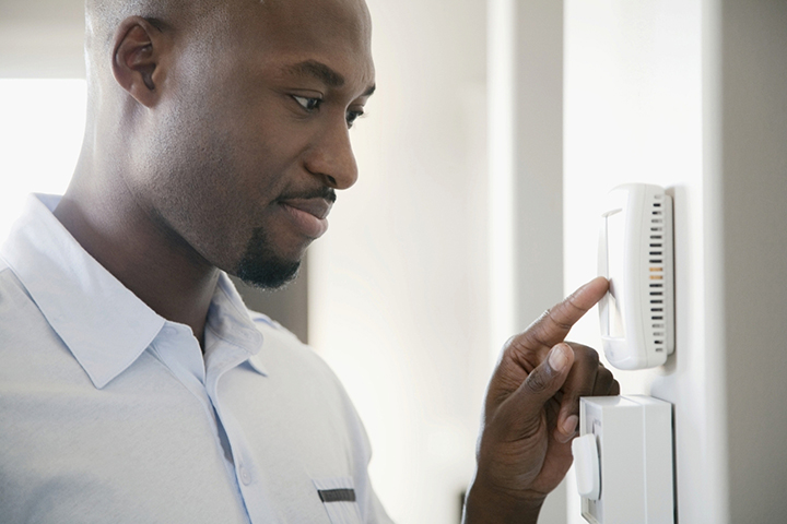 Black-man-checking-thermostat-web, Energy savings programs and ways to save this summer, Opportunities