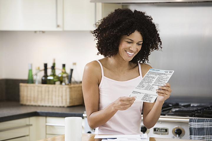 Woman-reading-energy-statement-web, How winter impacts utility bills: Smart ways to save money, Opportunities