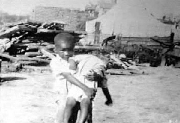 A boy holds a wounded child in the aftermath of the Tulsa Race Massacre (1921). The event remains one of the worst incidents of racial violence in U.S. history.