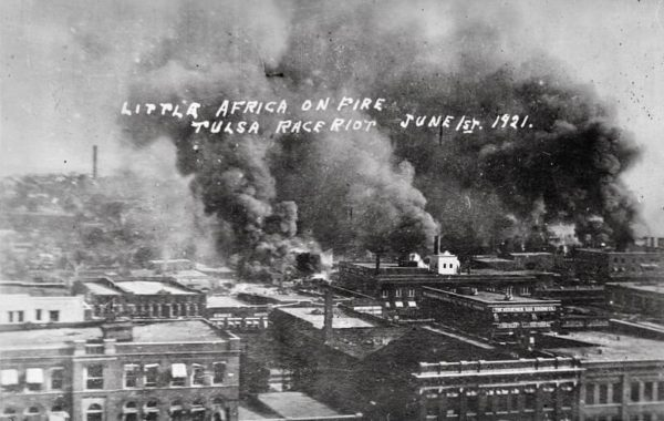 Buildings in the Greenwood Community burning with smoke-filled sky as viewed towards the west from Frankfort and Hartford streets from the Tulsa Race Massacre, 1921. Inscribed on the front, Little Africa on Fire, Tulsa Race Riot, June 1st, 1921.
