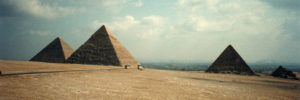Pyramids-of-Giza-with-modern-Cairo-in-background-Khufu-481-Khafre-448-Menkaure-215-Queens-by-@David-Holt-web-300x100, Slave labor, from the pyramids to the prisons, Behind Enemy Lines