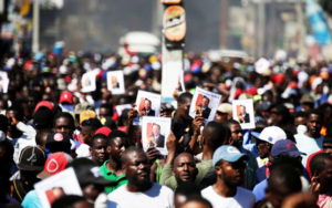 Haitians-march-to-demand-investigation-into-PetroCaribe-corruption-holding-up-Aristide-photos-symbolizing-good-govt-PAP-111818-by-Reuters-300x188, Fanmi Lavalas statement: Crisis and resolution, plan for Haiti's future, World News & Views