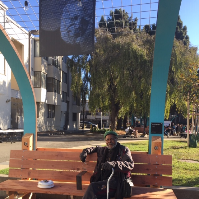 Eugene-White-on-Buchanan-Mall-park-bench-w-his-portrait-hanging-above, Beloved artist Eugene E. White passes, Culture Currents