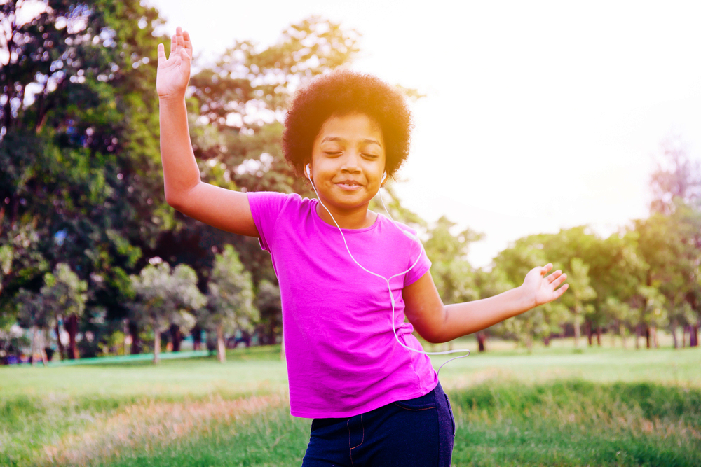"""girl-dancing-outsde-with-eyes-closed, 'I like to move it, move it!"""" How dance and other rhythmic movement can reduce the impact of ACEs, Culture Currents"""