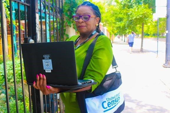 2020-Census-taker-looks-at-laptop-as-she-rings-bell-at-gate, Census Bureau embarks on a hiring blitz, National News & Views