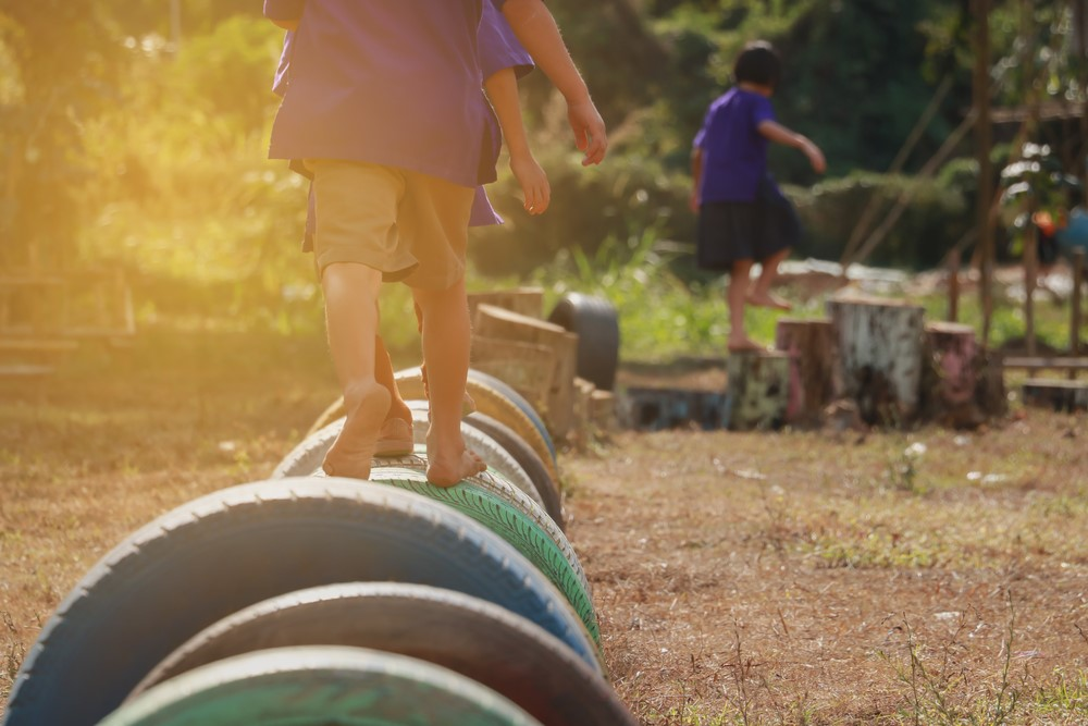 Kids-balancing-on-tires-and-stumps, Play and kids with ACEs: 'That's where everything is worked out', Culture Currents