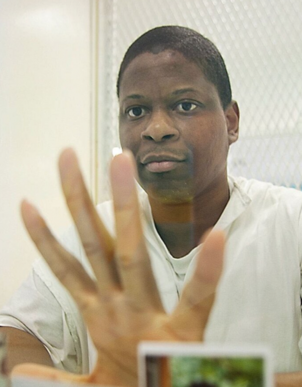 Rodney-Reed-hand-to-glass-1, New clemency system could turn Rodney Reed's 20 years of injustice into 20 days, Behind Enemy Lines Featured