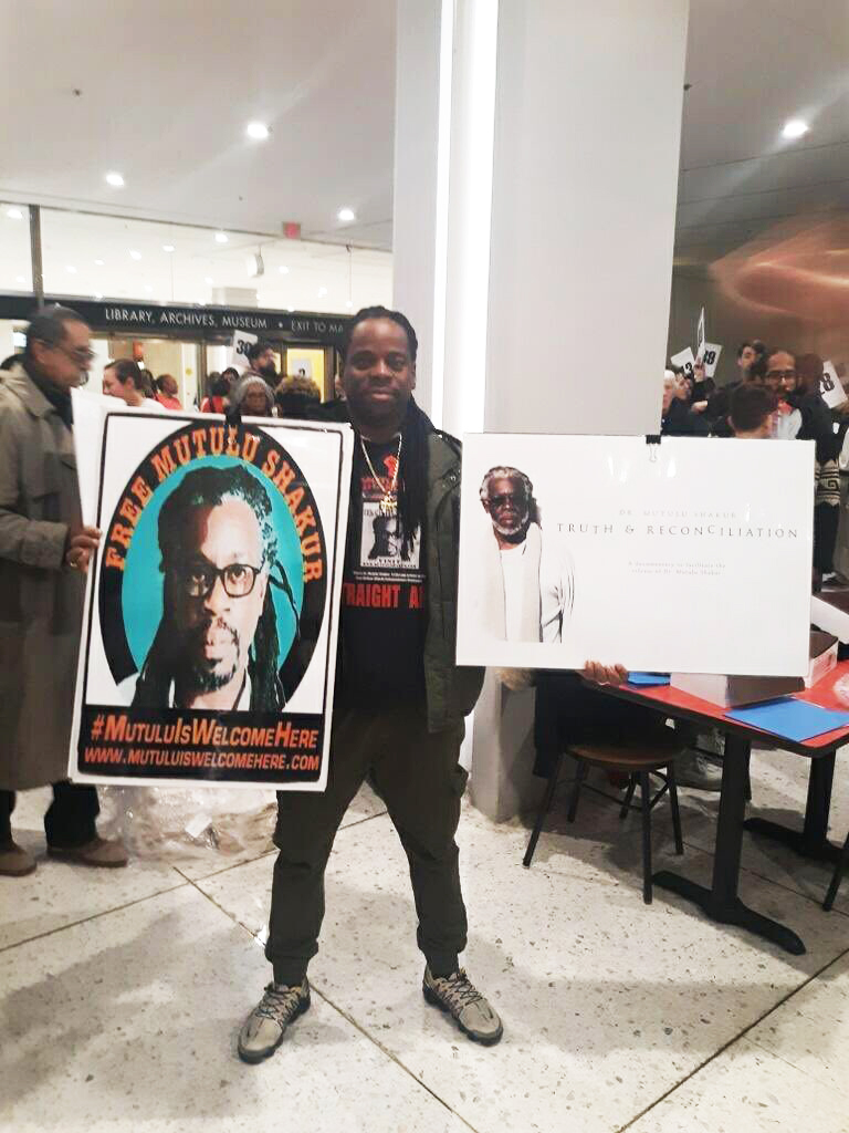 Talib-Shakur-displays-posters-on-dad-Dr.-Mutulu-Shakur-at-rally-for-RAPP-Release-Aging-People-in-Prison-in-Albany-NY-01142, 34 years too long: The case of Political Prisoner Dr. Mutulu Shakur, Behind Enemy Lines