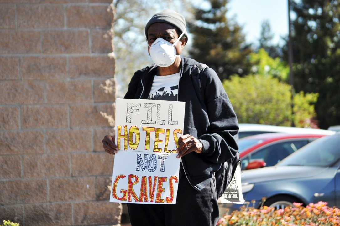 Fill-hotels-not-graves-sign-held-by-Black-organizer-for-East-Oakland-Collective-The-Village, COVID-19 further burdens Oakland's Black homeless population's quest to survive, Local News & Views