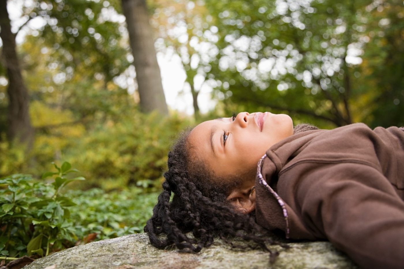 Black-child-lying-on-log-enjoys-nature-1400x933, Coronavirus parenting: Protecting your children during the pandemic, Culture Currents