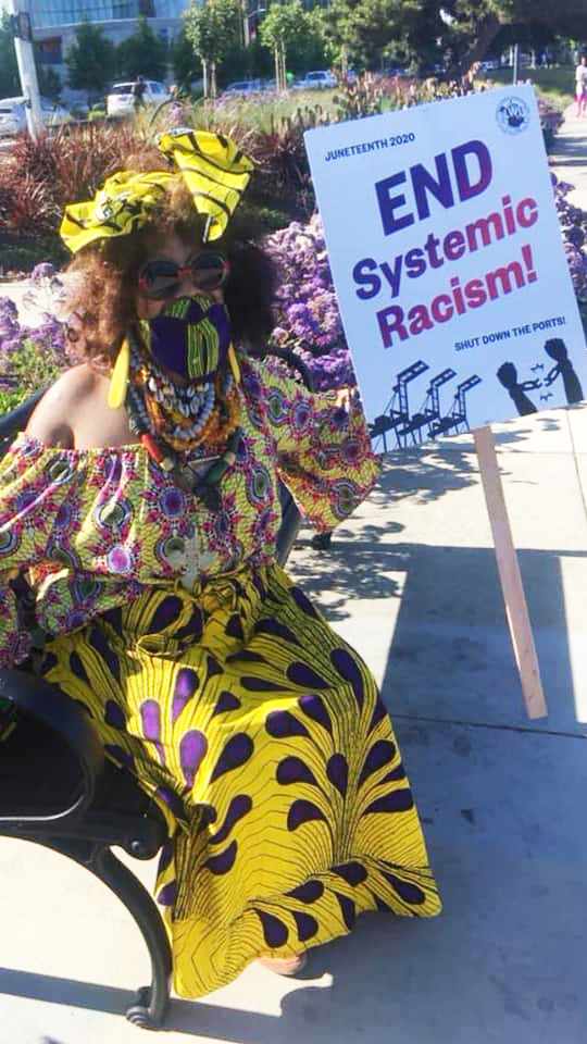 Denise-Gums-masked-w-End-Systemic-Racism-picket-sign, Wanda's Picks for August 2020, Culture Currents