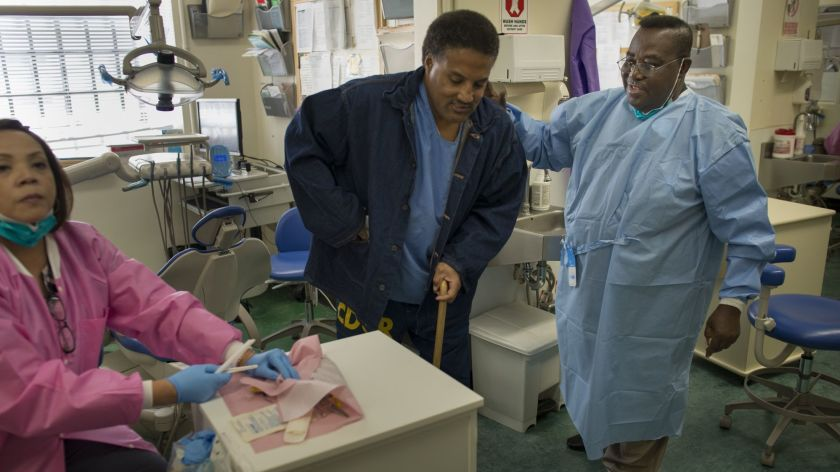 Dentist-Opanin-Gyaami-treats-incarcerated-patient-Larry-Butler-at-the-California-Medical-Facility-in-Vacaville-2012-by-David-Butow-LA-Times, More testing is needed to protect prisoners and caregivers, Behind Enemy Lines