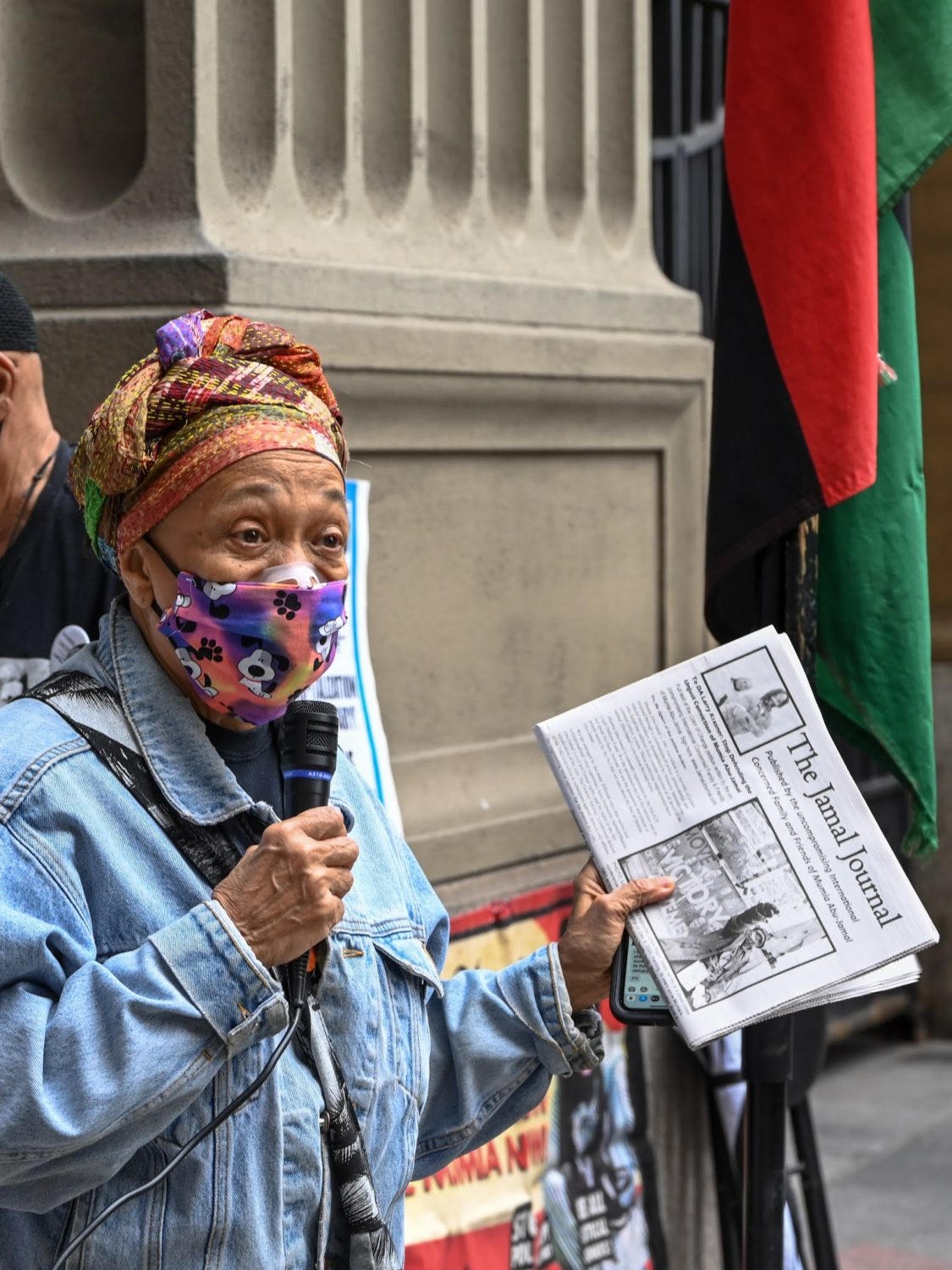 Pam-Africa-presents-first-issue-Jamal-Journal-outside-Philly-DA-Larry-Krasners-office-031221-by-Joe-Piette, Pam Africa: As Mumia awaits heart surgery, We are issuing a challenge to CNN's Michael Smerconish and DA Larry Krasner, Behind Enemy Lines