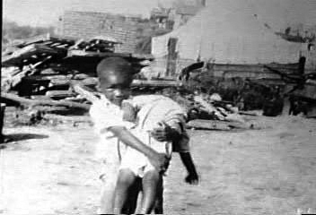 Tulsa-Race-Riot-Black-Wall-Street-child-carrying-child-060121, Rep. Barbara Lee marks 100th anniversary of Tulsa Greenwood Massacre, calling for reparations and a truth, racial healing and transformation commission, National News & Views