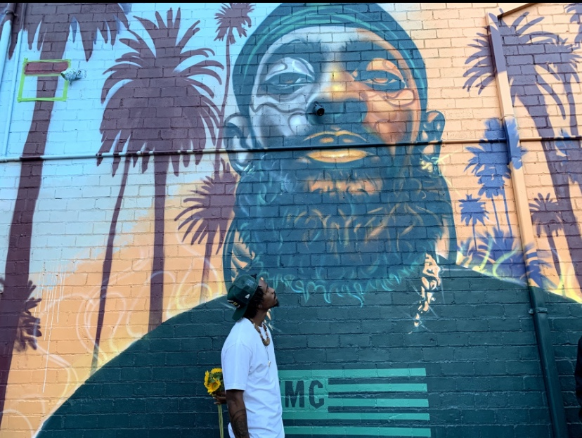 Timothy-Bluitt-stands-in-front-of-his-Nipsey-Hustle-mural-near-Lake-Merritt-by-Timothy-Bluitt, Muralist Tim B talks about performative activism and creating aerosol murals to combat it, his life's work and more, Culture Currents